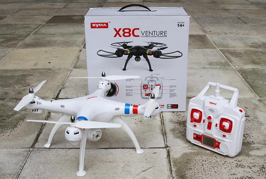 Il drone Syma X8C Venture tra il radiocomando e la confezione formato valigetta